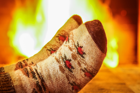 Man's feet in the wool socks, against cozy fireplace background, in mansion, winter vacations.