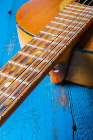 A view of old classical guitar, on blue background, closeup
