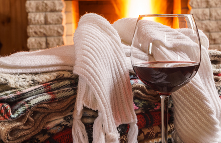 Red wine   in a glass, wool things,  near cozy fireplace, country house, winter vacation.