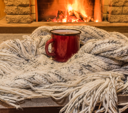 Red enameled mug for hot tea and cozy warm scarf near fireplace, in country house, winter vacation, horizontal.
