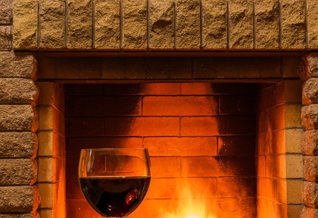 tranquil scene before cozy fireplace, with glass of red wine , in country house, in winter vacation.