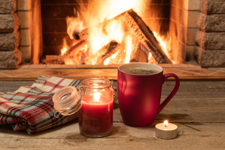 Red mug with hot tea, and a candle , wool scarf, near cozy fireplace, in country house, winter vacation.