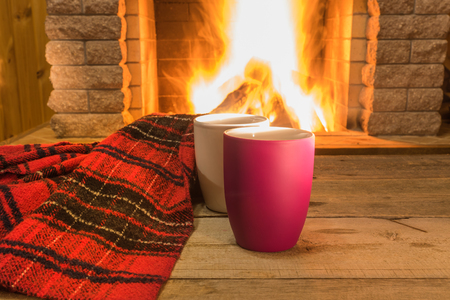Two mugs with hot tea and cozy warm re scarf near fireplace, in country house, winter vacation, horizontal.