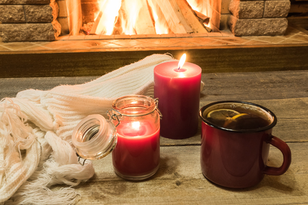 Red enameled mug with hot tea, and two candles , near cozy fireplace, in country house, winter vacation, horizontal.