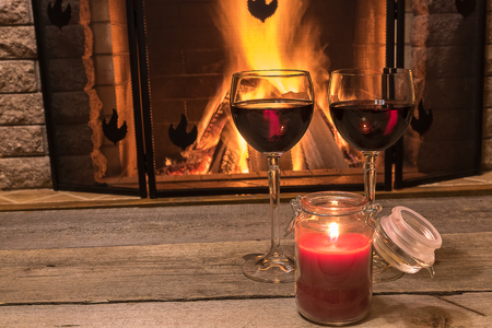 tranquil scene before cozy fireplace, with two glasses of red wine and candle, in country house, in winter vacation.