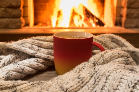 Red cup with hot tea and cozy warm scarf near fireplace, in country house, winter vacation, horizontal.