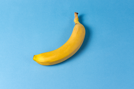 Creative concept. Flat lay view of banana fruit pattern over blue background.