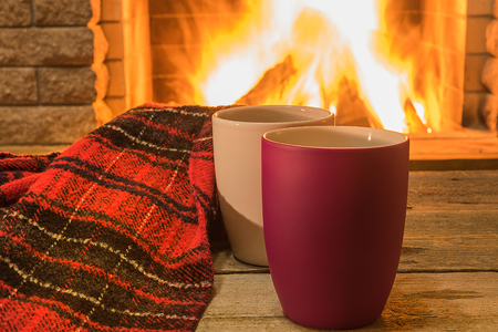 Two mugs with hot tea and cozy warm scarf near fireplace, in country house, winter vacation, horizontal.