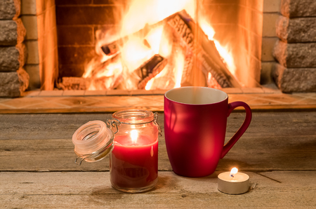 Mug of hot tea and candles near cozy fireplace, in country house, winter vacation, horizontal.