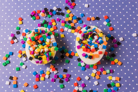 Minimalism concept. Unexpected concept. flat lay, view two eggs filled with colorful small mosaic, over colorful background. Foto de archivo