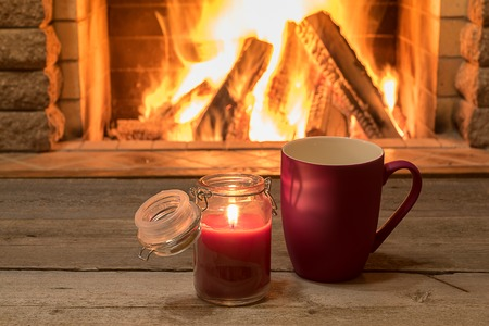Mug of hot tea and candle near cozy fireplace, in country house, winter vacation.