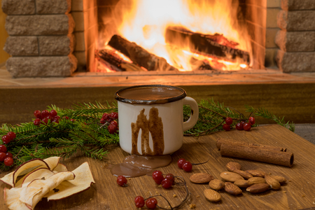 Cozy scene before Red enameled mug with hot chocolate, christmas decoration, in country house, winter vacation. Фото со стока