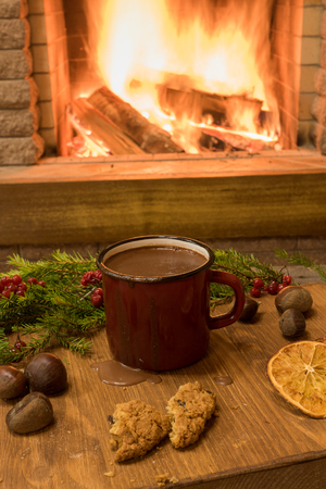 Cozy scene before Red enameled mug with hot chocolate, christmas decoration, in country house, winter vacation. Stock Photo
