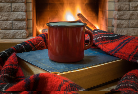 Big enameled mug with tea, and warm wool scarf , a book , near cozy fireplace, in country house, winter vacation. Stockfoto