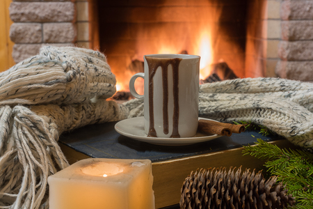 mug of hot chocolate, cone, candle and wool scarf, near cozy fireplace, in country house, winter vacation. Stock Photo