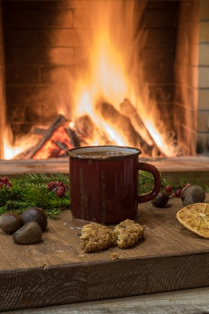 Big red mug with hot chocolate, near cozy fireplace, mulled orange fruit, nuts, in country house, winter vacation, vertical.