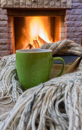 Big mug with tea, and warm wool scarf , a book , near cozy fireplace, in country house, winter vacation. Stock Photo