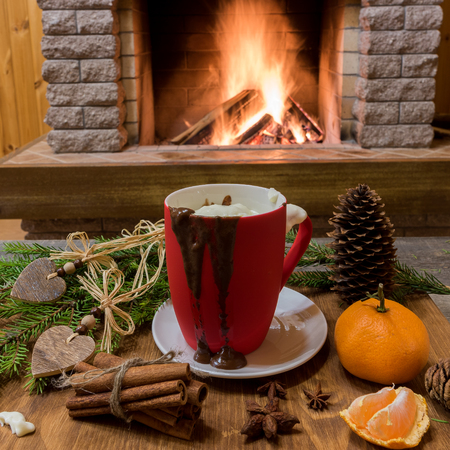 Big mug with hot chocolate, near cozy fireplace, tangerine fruit, cinnamon sticks, in country house, winter vacation, vertical. Stock Photo - 114693059