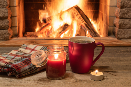 Mug of hot tea, wol scarf and candle near cozy fireplace, in country house, winter vacation.