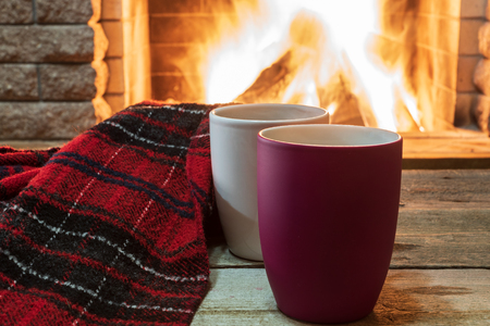Mugs of hot tea, wol scarf near cozy fireplace, in country house, winter vacation.