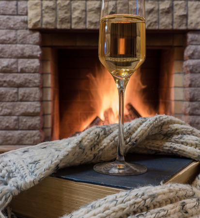 glass of wine, book and warm wool scarf near cozy fireplace in country house, winter vacation.