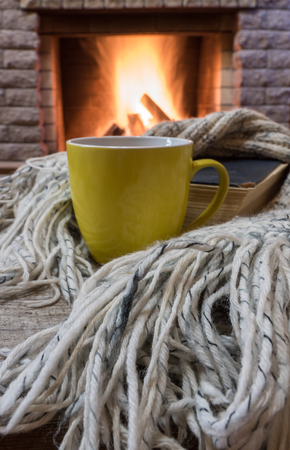 Big mug with tea and warm wool scarf near cozy fireplace in country house, winter vacation.