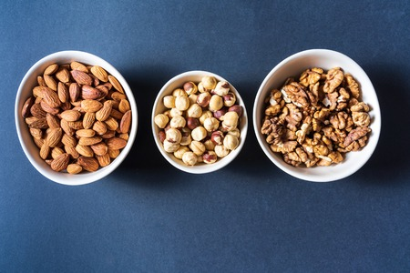 Flat lay Variation of nuts in bowls on gray background with copy space for text. Banco de Imagens
