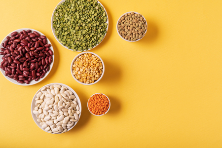 Top view of assortment of peas, lentils, beans and legumes over yellow background, with copy space. Archivio Fotografico