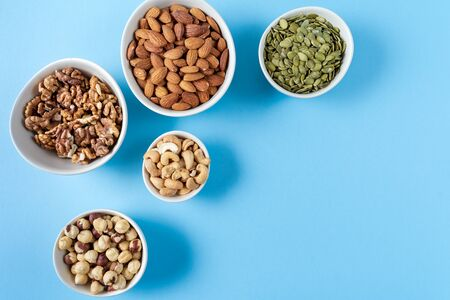 Flat lay Variation of nuts in bowls on blue background with copy space for text.