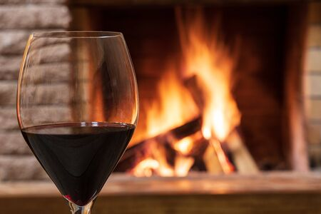 Glass of red wine against cozy fireplace background, in country house, horizontal, hygge , home sweet home. Imagens