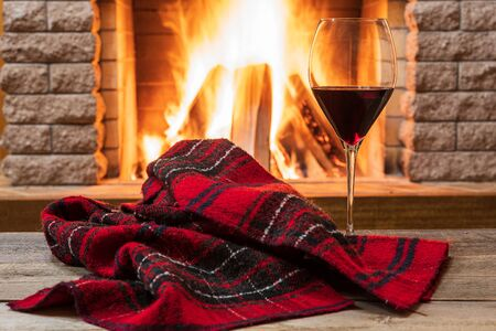 Glass of red wine and warm scarf against cozy fireplace background, in country house, horizontal, hygge , home sweet home. Stock Photo