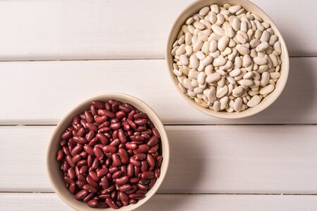 Flat lay of assortment of beans and legumes over white wooden background.