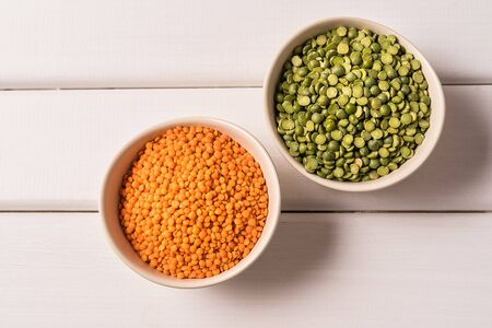 Flat lay of assortment of peas and lentils over white wooden background.