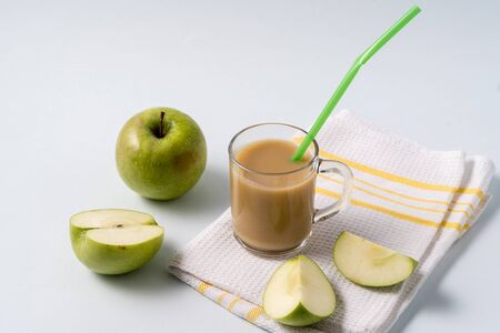 Indian traditional Masala chai tea in a a glass cup and fresh apples over white table background with copy space for text.