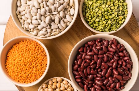 Flat lay of assortment of peas, lentils, beans and legumes over wooden background.