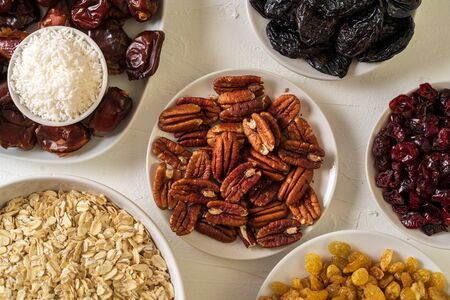Ingredients for preparing Healthy organic energy balls- dates, dried apricot, oat flakes, raisin, dried cranberries, pecan nuts, coconut shavings on white background, flat lay.