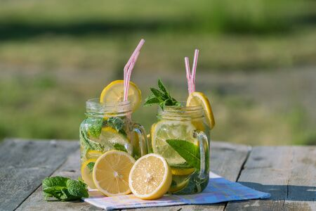 Summer concept. Homemade Lemonade with lemon, mint and ice in a jar, over old wooden table, outdoor. Stockfoto
