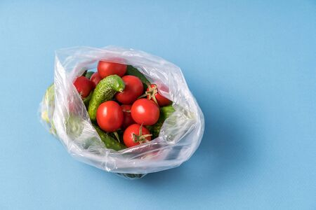 Front view Cucumbers and tomatoes in plastic bag on blue background. Image shows the harmness of using artificial food storage bags. Horizontal image.