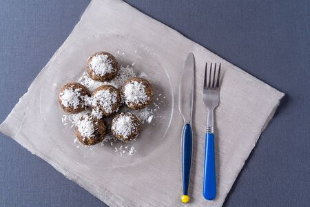 Healthy organic energy balls made with dates, prunes, raisins, peanut, in a plate on gray background, flat lay.