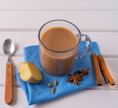 Indian traditional Masala chai tea in a mug, ginger, cinnamon sticks and anise, over white table background. Фото со стока