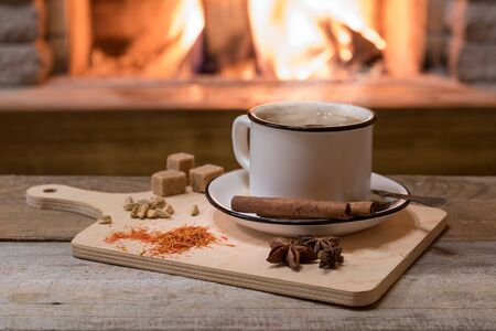 Indian traditional Masala chai tea in a mug and kitchen herbs, over cozy fireplace background with copy space for text.