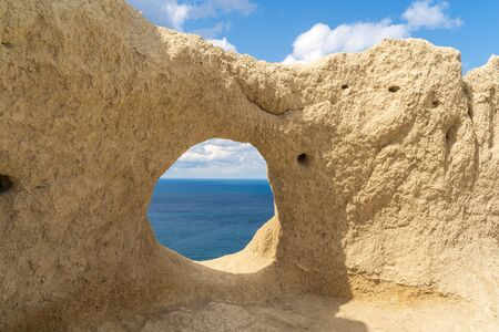 View through the round rock with swallows nests to the Black sea, in Anapa, Russia.