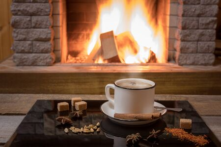 Cozy scene before fireplace with a cup of Masala chai tea with spices, in country house, winter vacation.