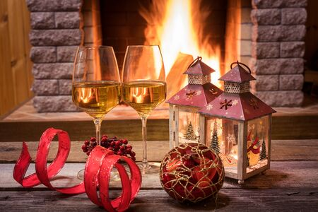 Christmas eve. Two glasses of white wine, candles and christmas decorations near cozy fireplace, in country house, winter vacation.