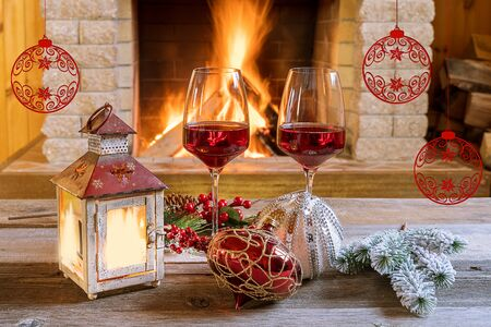 Christmas eve. Two glasses of red wine, christmas lantern and christmas decorations near cozy fireplace, in country house, winter vacation. 스톡 콘텐츠
