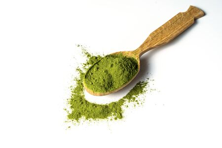 Matcha green tea powder in wooden spoon isolated on white background. Stok Fotoğraf - 137895297