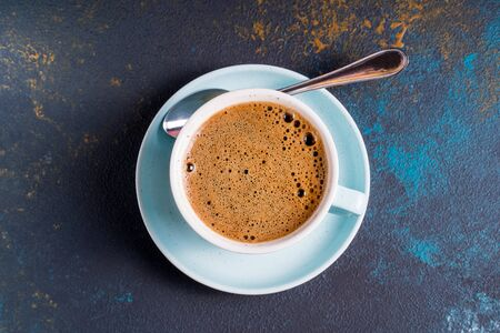 Black coffee with foam in a cup , on blue concrete background.,flat lay.