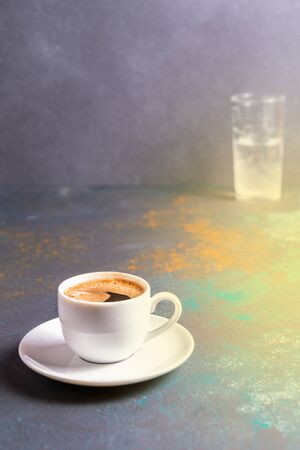 Cup of black coffee in a cup on blue board, blurred bokeh background, morning coffee concept,copy space. 스톡 콘텐츠