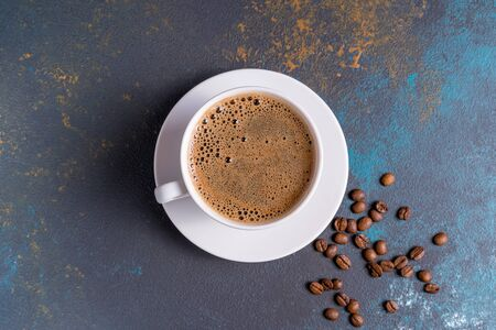 Black coffee with foam in a cup and coffee beans, on blue concrete background.,flat lay. 스톡 콘텐츠