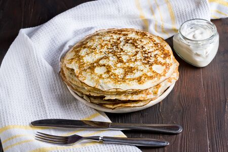 Pancakes with sour cream. Maslenitsa. Russian tradition in the last week before Easter to eat pancakes with different fillings. Фото со стока